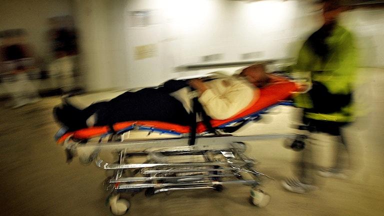 Ambulanspersonal kör in en man på bår på en akutmottagning. Foto: Tomas Oneborg/TT