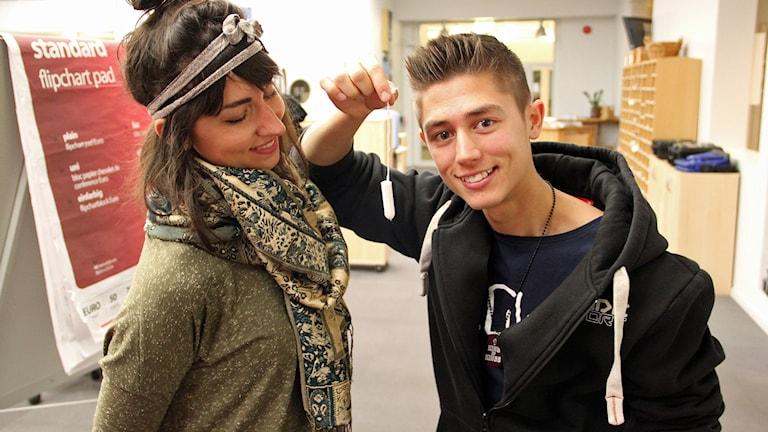 Tina Macic och Alex Hermansson står med en tampong. Deras låt om mens har redan blivit populär. Foto: Jenny Cederbom/Sveriges Radio
