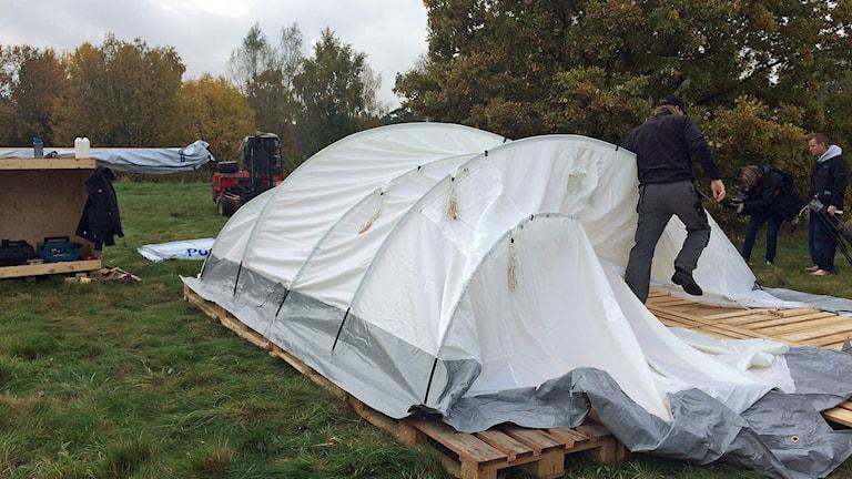 Ett av de tält som ska sättas upp i Revinge sätts upp på prov. Foto: Tobias Wallin/Sveriges Radio