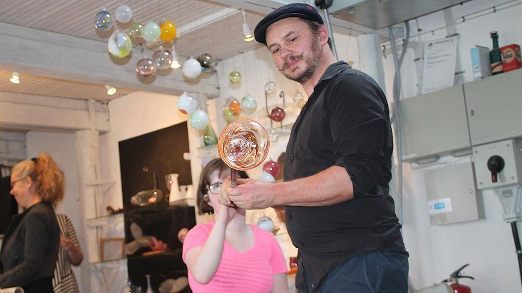 Emma Rosenqvist blåser en glasbubbla med hjälp av Espen Jensen. Foto: Malin Thelin/Sveriges Radio