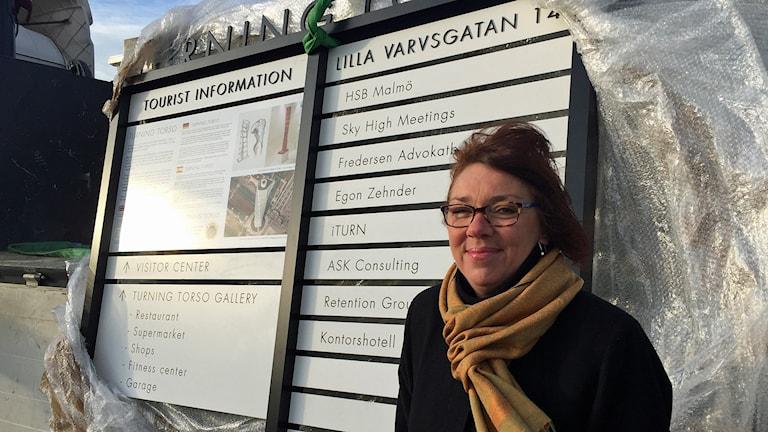 Mia Gustafson står framför den nya skylten vid Turning Torso som har information på svenska, engelska, spanska och tyska. Foto: Anton Kalm/Sveriges Radio