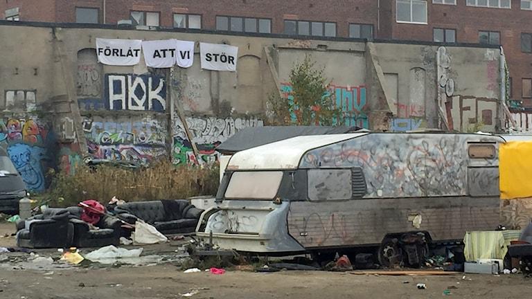 """Nätverket för romers rättigheter har hängt upp en banderoll vid lägret. """"Förlåt att vi stör"""" står det på den. Foto: Jenny Cederbom/Sveriges Radio"""