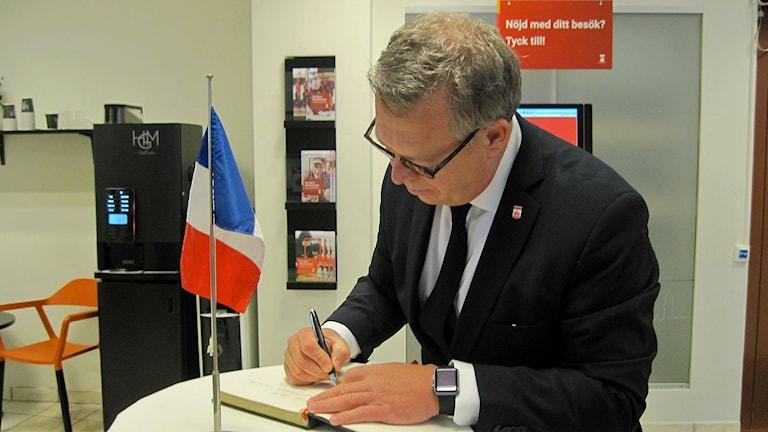 Kommunfullmäktiges ordförande Mats Sander skriver i kondoleansboken på Helsingborgs kontaktcenter. Foto: Bosse Johansson/Sveriges Radio