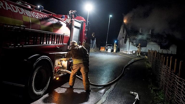 Brandbil samt brandman utanför brinnande hus i Kågeröd. Foto: Johan Nilsson / TT