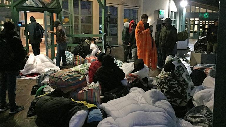 Asylsökande män som sovit utomhus utanför Migrationsverkets ankomstboende på Jägersro i Malmö. Foto: Anton Kalm/Sveriges Radio