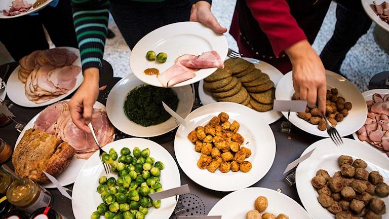 Personer plockar till sig mat på tallrikar från en julbordsbuffé. Foto: Robin Haldert/TT