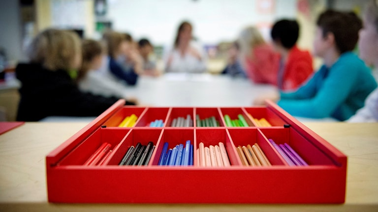 Färgpennor ligger i förgrunden i ett etui, i bakgrunden sitter en lågstadieklass och har lektion. Foto: Jessica Gow/TT