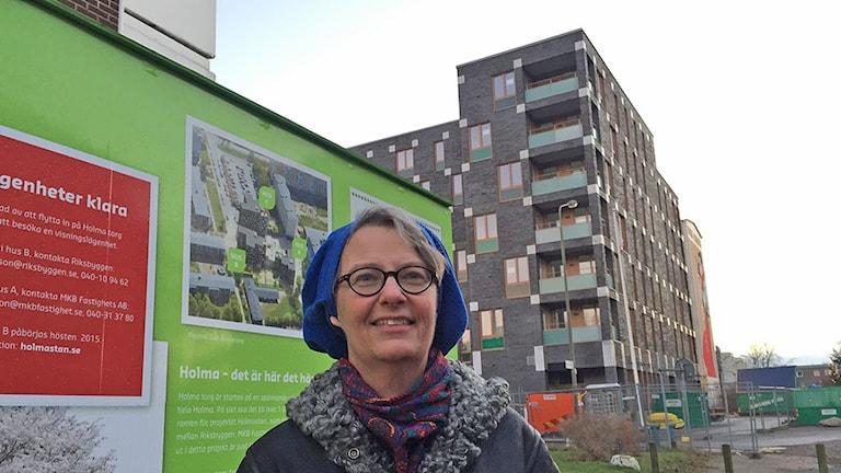 Marianne Dock, programarkitekt i Malmö stad. I bakgrunden syns ett av de tre nybyggda husen i Holma. Foto: Jonathan Hansen/Sveriges Radio