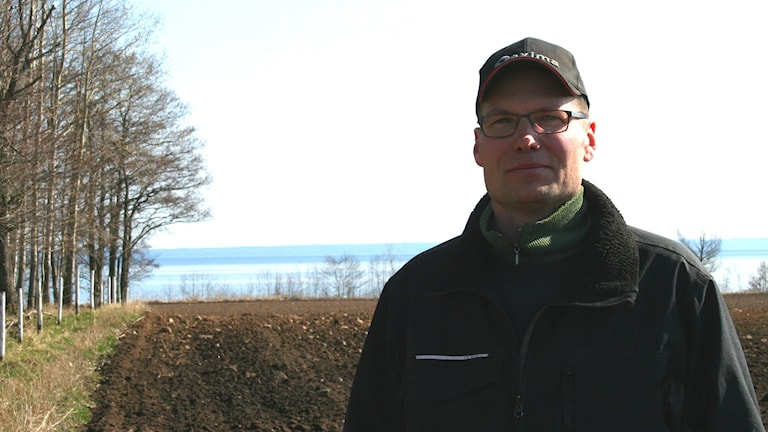 Anders Berglund ute på en åker, i bakgrunden en sjö