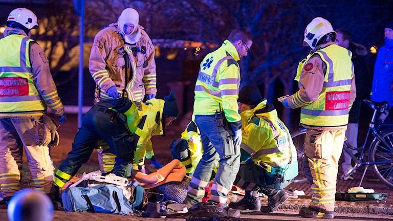 Räddningspersonal tar hand om två personer skadades sedan de blivit påkörda av en polisbil.  Foto: André Tajti / topnews.se