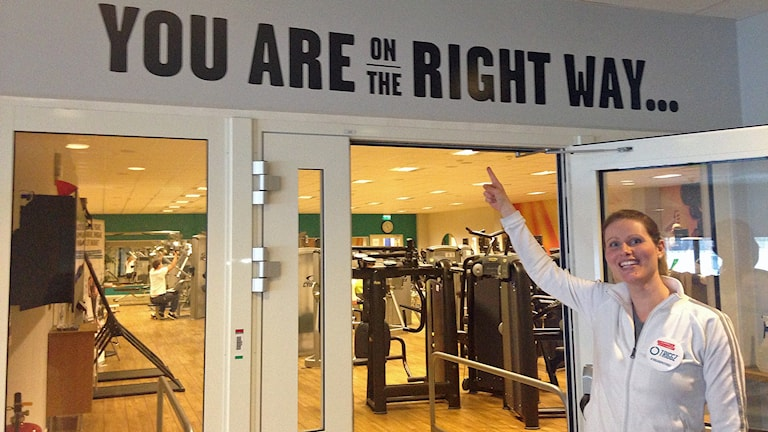 """Anna Lindgren som jobbar på ett gym i Malmö framför en skylt med orden """"You are on the right way"""". Foto: Jonathan Hansen/Sveriges Radio"""