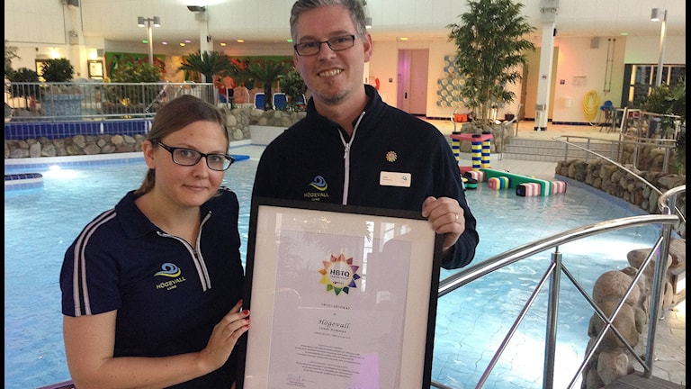 Amanda Sjöberg och Stefan Sjöström, driftsansvarig, Högevallsbadet i Lund håller upp diplomet som visar att personalen har genomgått HBTQ-certifiering. Foto: Daniel Persson/Sveriges Radio