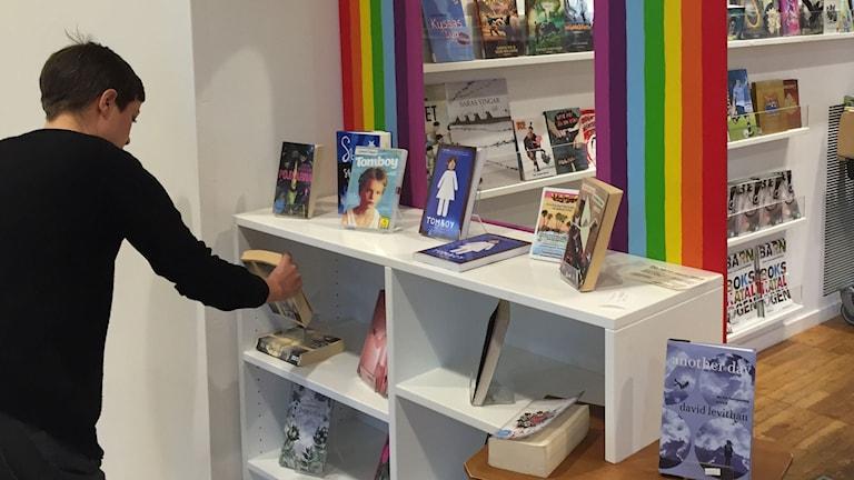 Bibliotekarien Åsa Sandström ställer böcker i regnbågshyllan