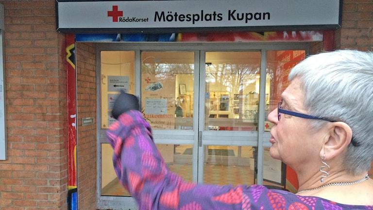 Röda Korsets Malmöordförande Kerstin Larsson visar hur organisationen skulle vilja skydda sina fönster mot skadegörelse. Foto: Evelina Olsson/Sveriges Radio.