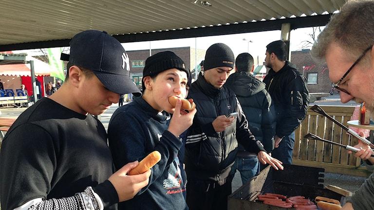 Mahmoud Elghoul äter korv tillsammans med sin kompis Malek Shureih närmast kameran.