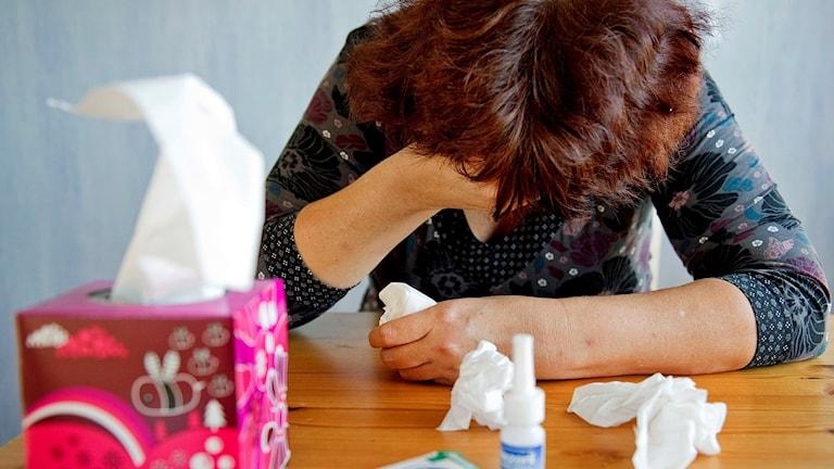 En kvinna sitter nedböjd över ett köksbord med snutna näsdukar, nässpray och huvudvärkstabletter. Foto: Jessica Gow/TT