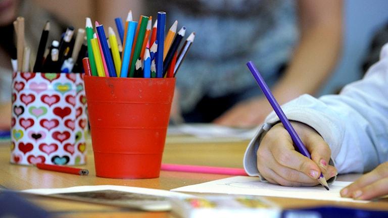 Ett klassrum där en elev ritar med färgglada pennor.