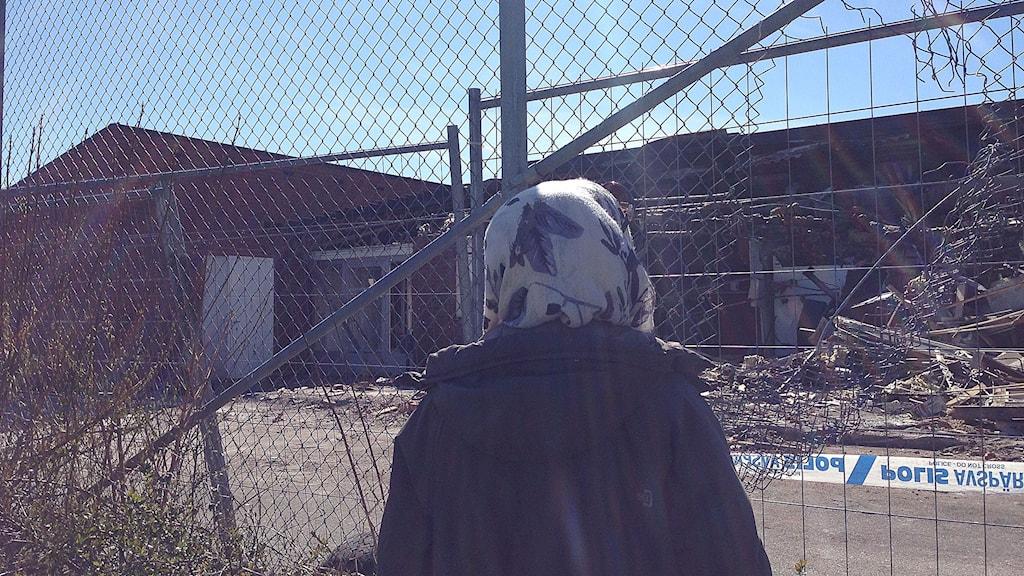 Kvinna betraktar resterna av förskolan.
