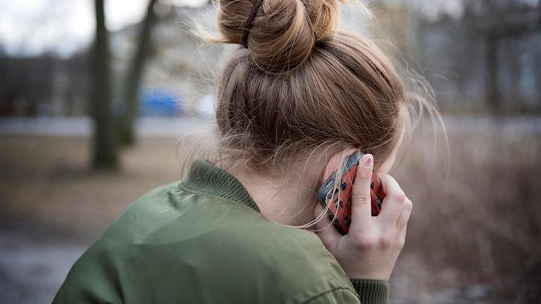 kvinna med ryggen mot håller en mobil mot örat.