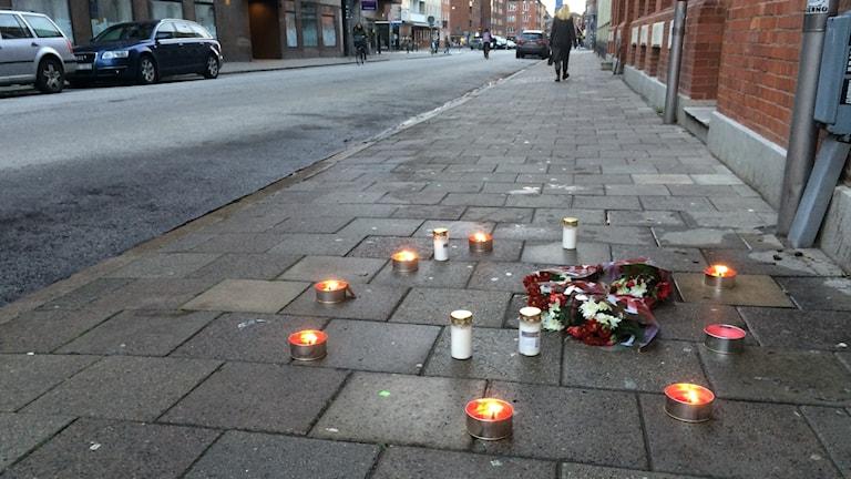 Blommor och ljus på gatan där en man sköts till döds