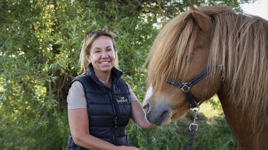 Kvinna ler in i kameran med handen lutad mot en brun häst som syns i profil