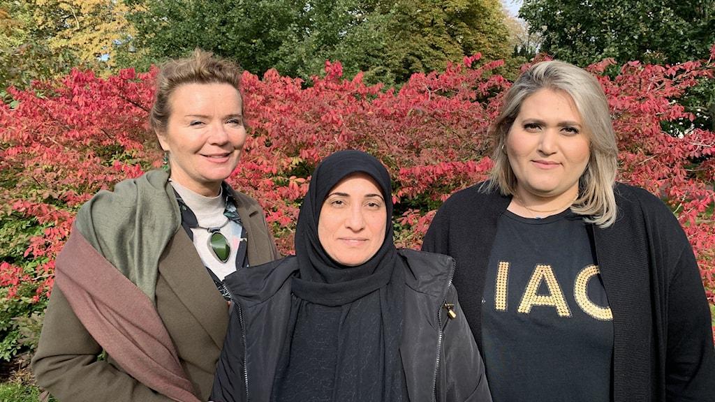 Tre kvinnor står framför en buske