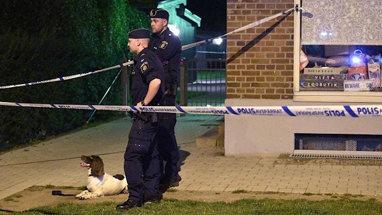 Två poliser och en hund vid polisavspärrningar på Lönngatan.