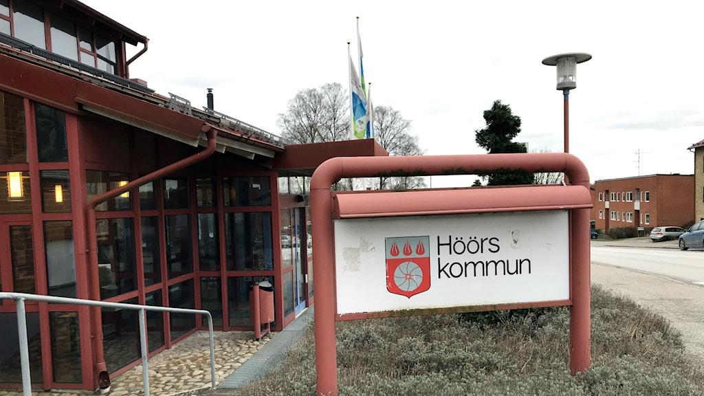 """Bilden visar entrén till kommunhuset i Höör, på Södergatan i Höör. I förgrunden ser man en skylt med kommunens vapen och där det står """"Höörs kommun"""". I bakgrunden skymtar två flaggstänger, med flaggor. Foto: Anna Bubenko/Sveriges Radio."""