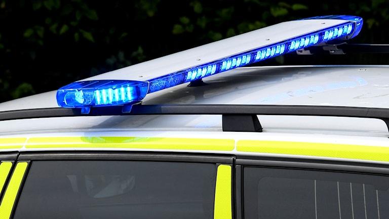 Polisbil med blåljusen igång.
