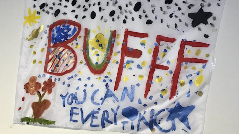 En målad bild med texten BUFFF, You can everyting, av barn.
