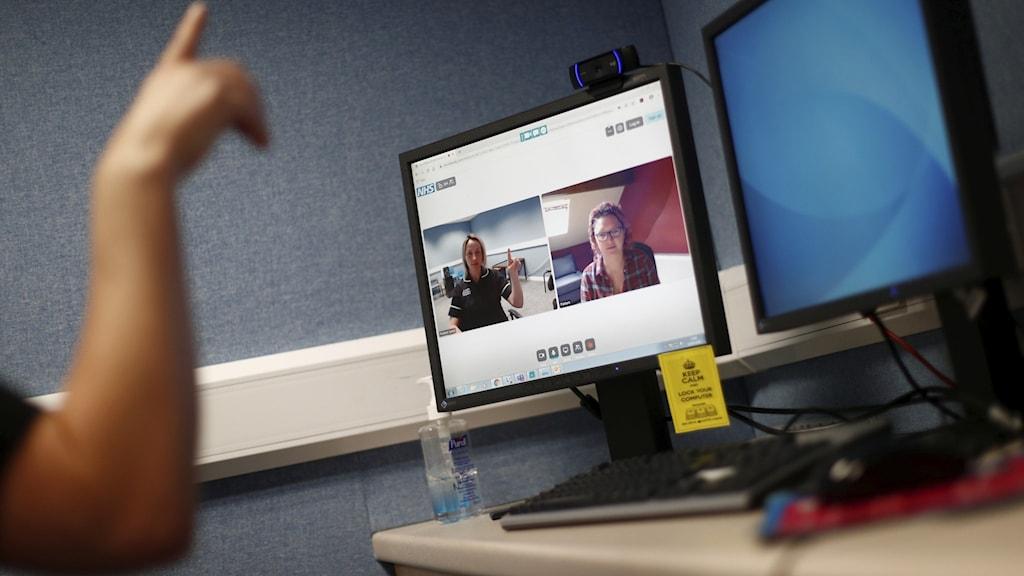bild på arm som pekar mot skärm som visar två personer på zoom