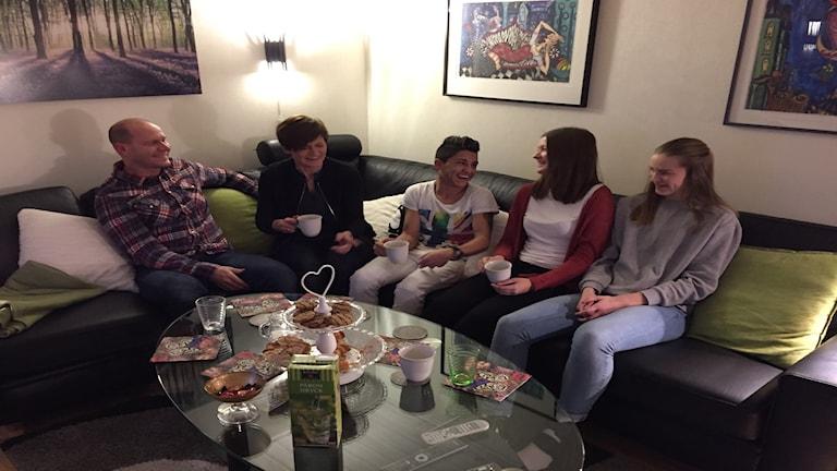 Carina Tjerngren sitter i soffan tillsammans med sin familj och Sven som de är fadderfamilj till sedan i höstas
