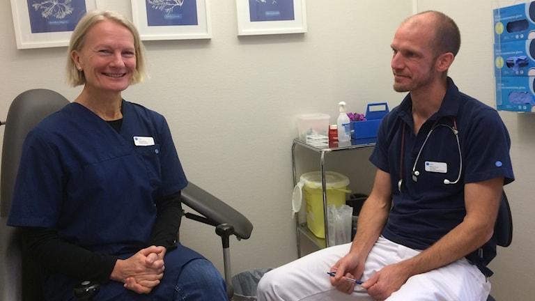 Gunnel Fors sitter i sjukhuskläder bredvid Martin kvist, även han i sjukhuskläder i ett undersökningsrum.