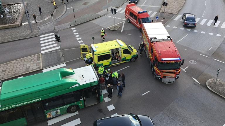 Trafikolycka där buss kört på gångtrafikant. Brandbil och ambulans syns på bilden. Ambulanssjukvårdare och räddningstjänst kring den skadade personen.