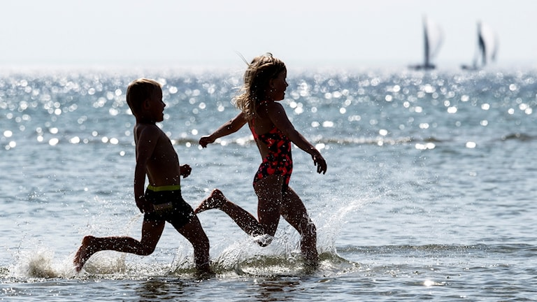 Syskonen Albert och Thea tar ett dopp i Öresund vid stranden i Lomma när temperaturen på lördagen letade sig över 20-gradersstrecket. Foto: Johan Nilsson/TT
