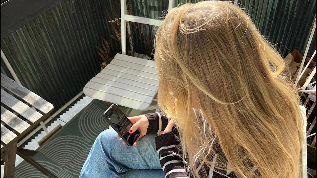 flicka som tittar på sin mobil