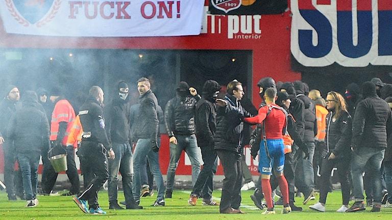 Planen på Olympia stormas och Jordan Larsson hotas av supportrar efter HIF:s kvalmiss. Foto: Emil Langvad/TT.