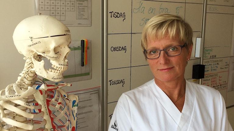 Cecilia Rogmark, överläkare i ortopedi på Skånes universitetssjukhus, står bredvid ett undervisningsskelett. Foto: Petra Haupt/Sveriges Radio