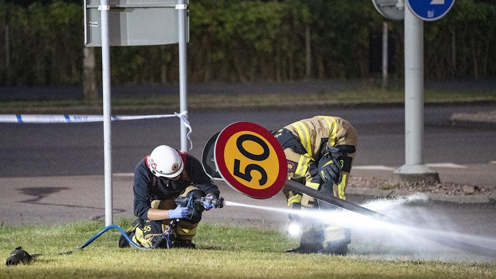 räddningstjänst undersöker skylt.