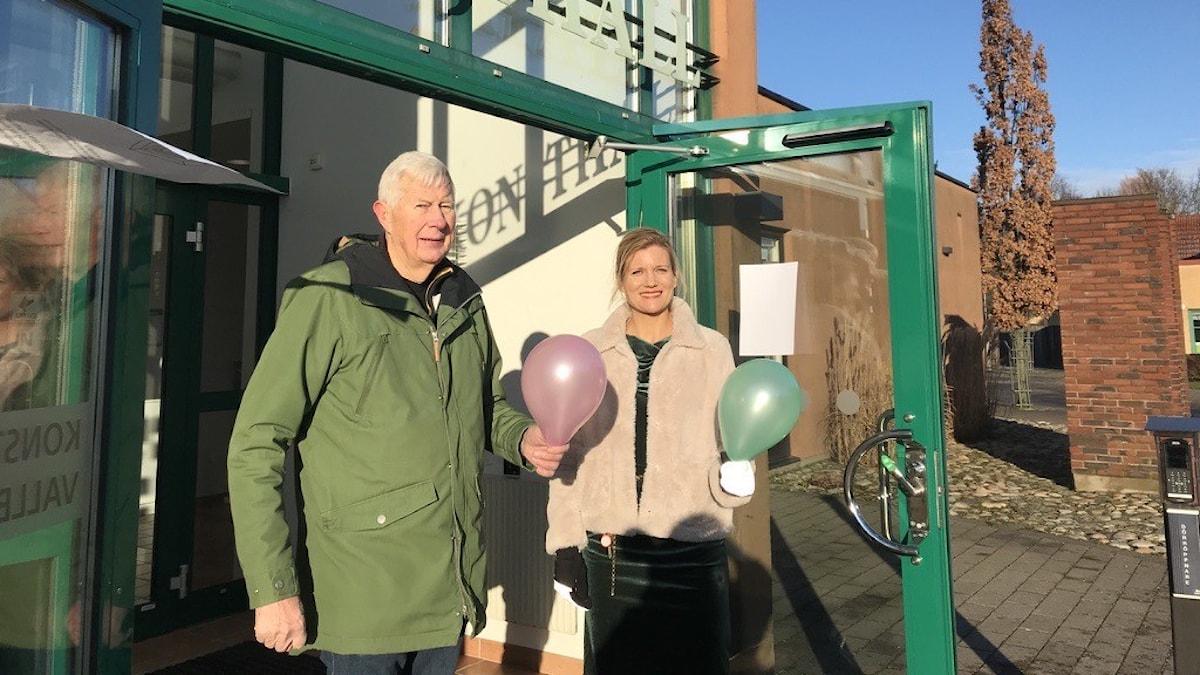 Två personer med ballonger utanför konsthall.