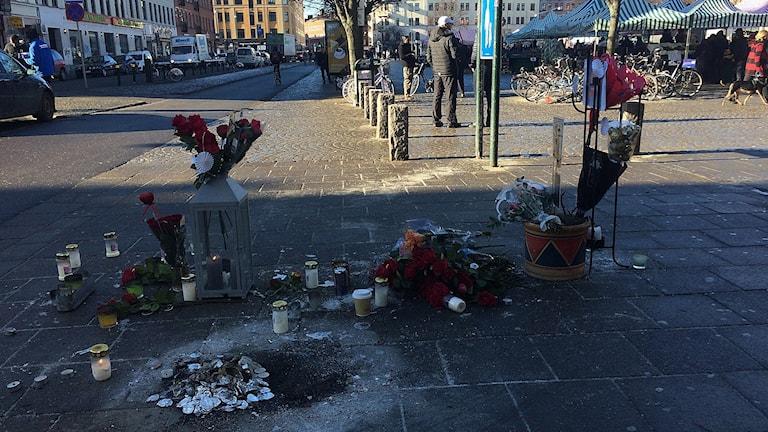 Blommor och ljus på den plats där en man i 20-årsåldern sköts till döds på söndagskvällen.