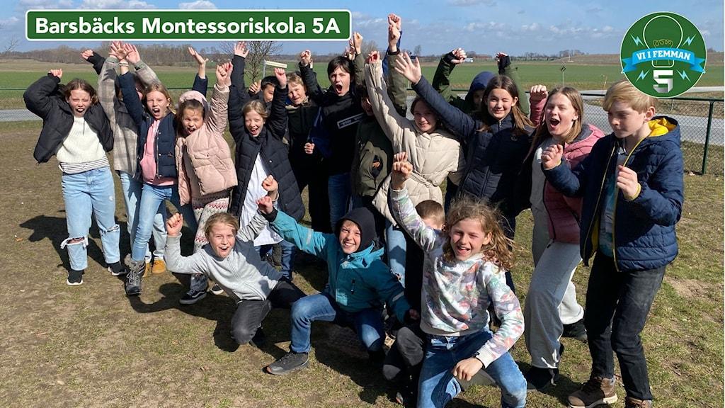 Barsebäcks Montessoriskola 5A uppställda för en gruppbild inför Vi i femman. Alla har händerna i luften och ser ut att jubla.