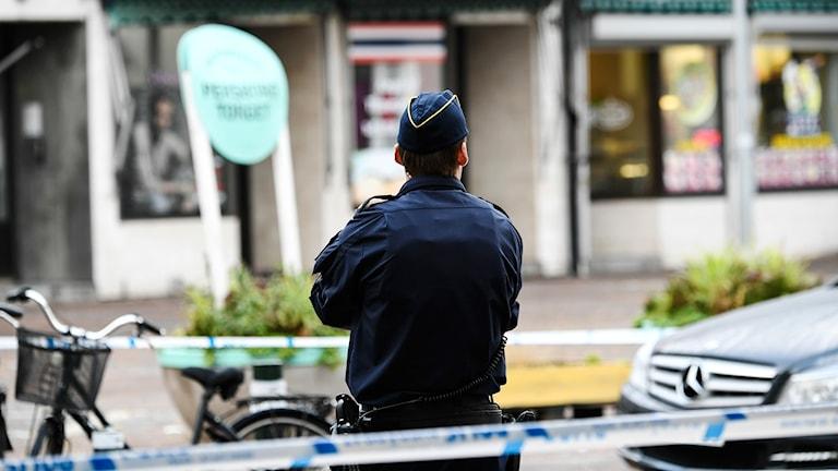 En polis står med ryggen mot kameran vid en avspärrnig.