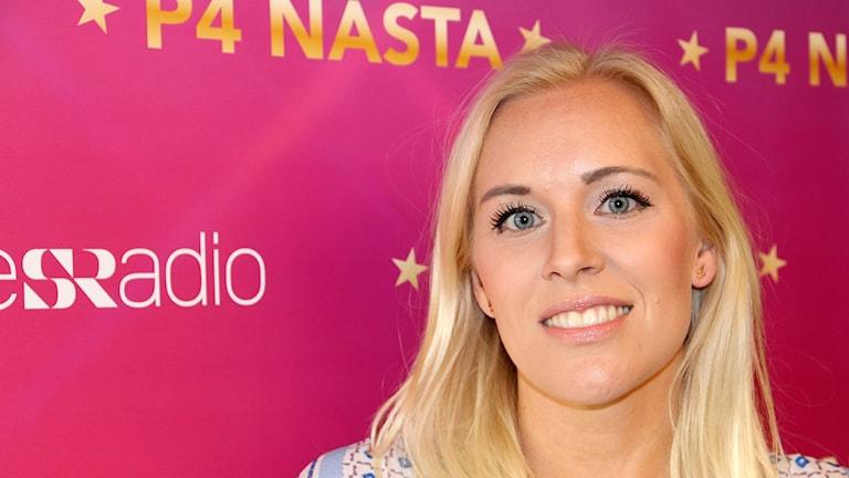 Blond kvinna framför reklamskylt för tävlingen P4 Nästa.