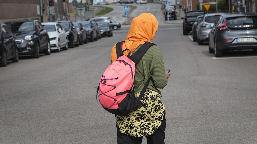 Kvinna med slöja promenerar på gata.