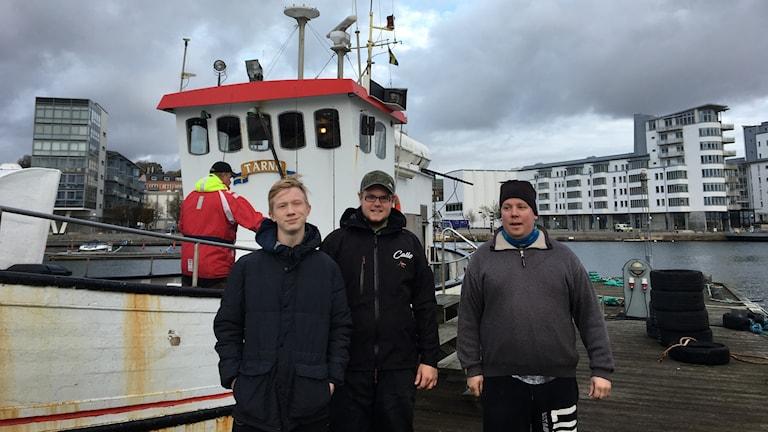 Fiskelägerdeltagarna Christian Nilsson och Calle Hjelm med skepparen på Helsingborgsbåtarna, Niklas Nielsen i Norra hamnen.