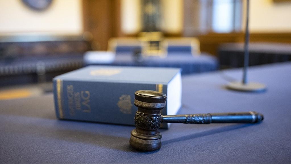 Lag bok och en domarklubba ligger på ett bord