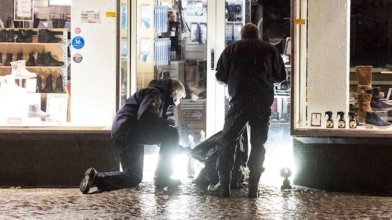 Polisens kriminaltekniker tar hand om föremål i en butiksentré ett stenkast från nattklubben i centrala Ängelholm efter nattens attentat.
