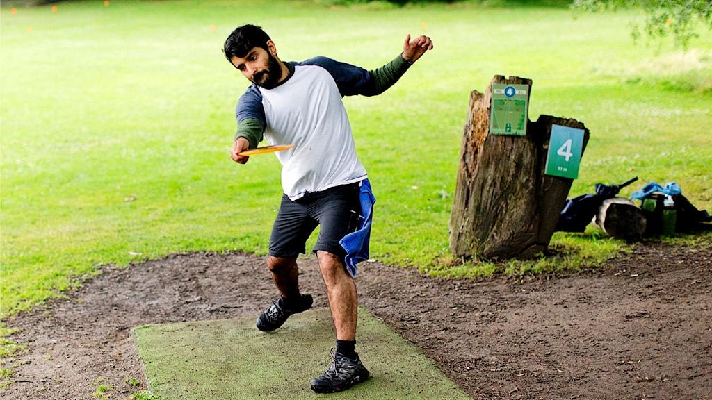 Man i park utövar discgolf.