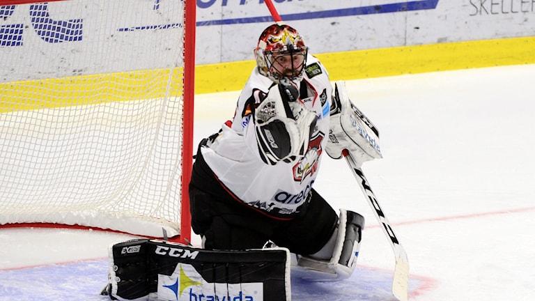 Ishockeymålvakt står på knä och får en puck emot sig.